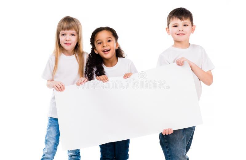 Menino pequeno e menina bonitos que guardam uma folha de papel vazia foto de stock royalty free