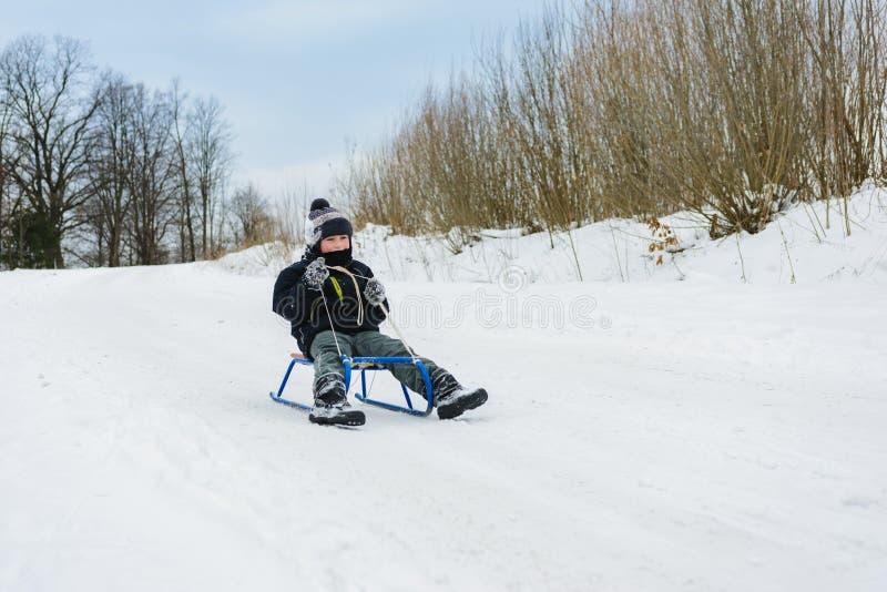 Menino pequeno feliz no pátio coberto de neve do inverno imagens de stock