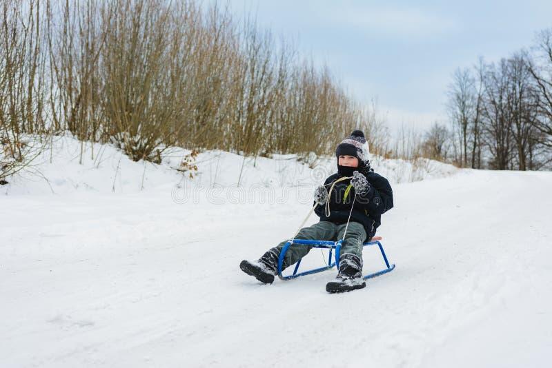 Menino pequeno feliz no pátio coberto de neve do inverno fotografia de stock royalty free