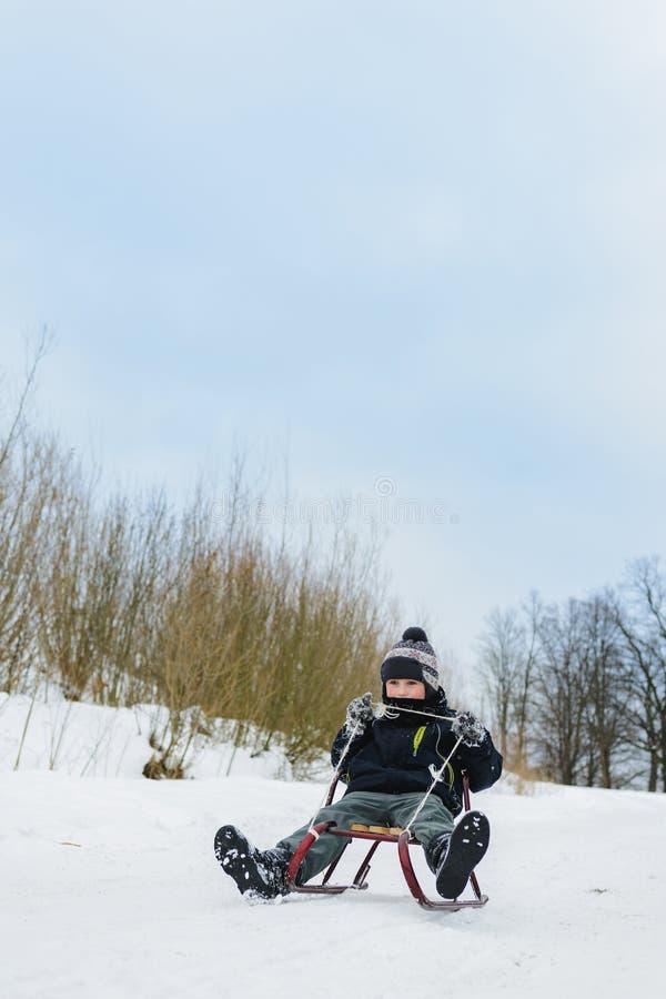 Menino pequeno feliz no pátio coberto de neve do inverno imagem de stock