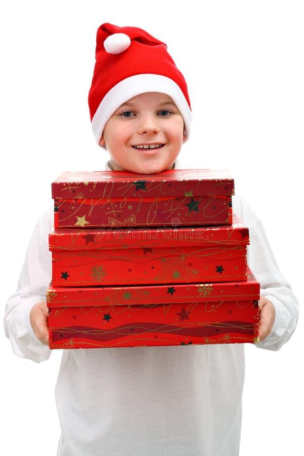 Download Menino Pequeno No Chapéu Vermelho De Santa Que Carreg Três Presentes Foto de Stock - Imagem de chapéu, menino: 16867302