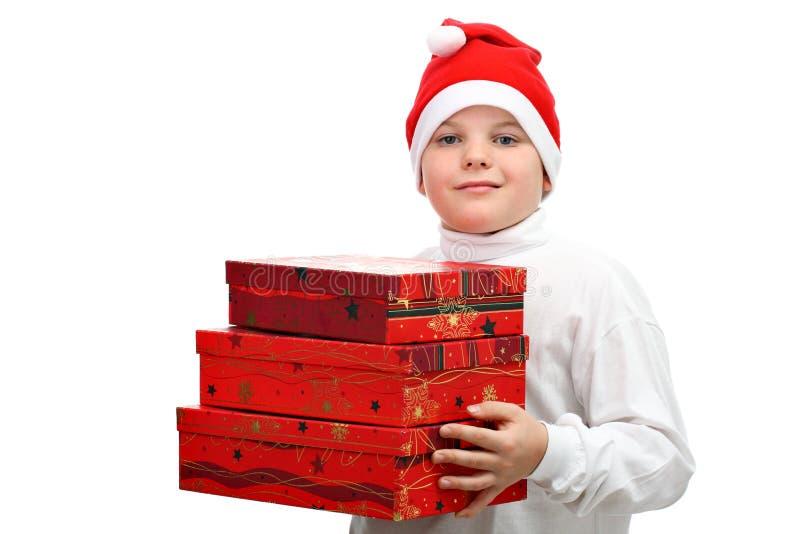 Download Menino Pequeno No Chapéu Vermelho De Santa Que Carreg Três Presentes Foto de Stock - Imagem de carregar, christmas: 16867338