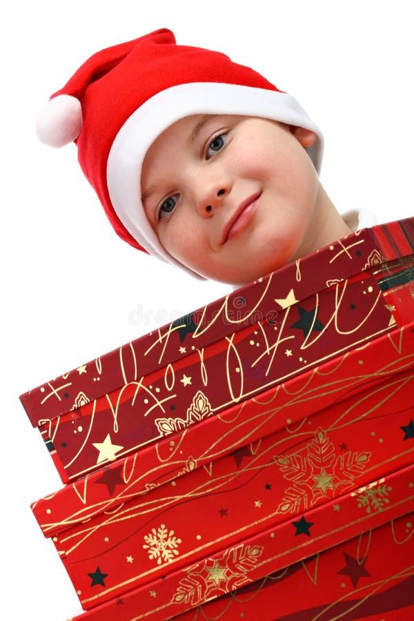 Download Menino Pequeno No Chapéu Vermelho De Santa Que Carreg Três Presentes Imagem de Stock - Imagem de tampão, tiro: 16867359