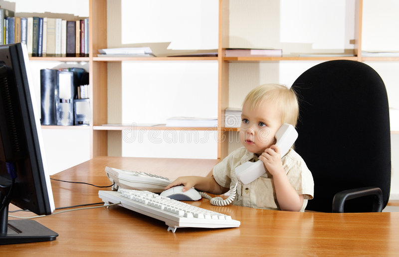 Menino pequeno no escritório fotografia de stock royalty free