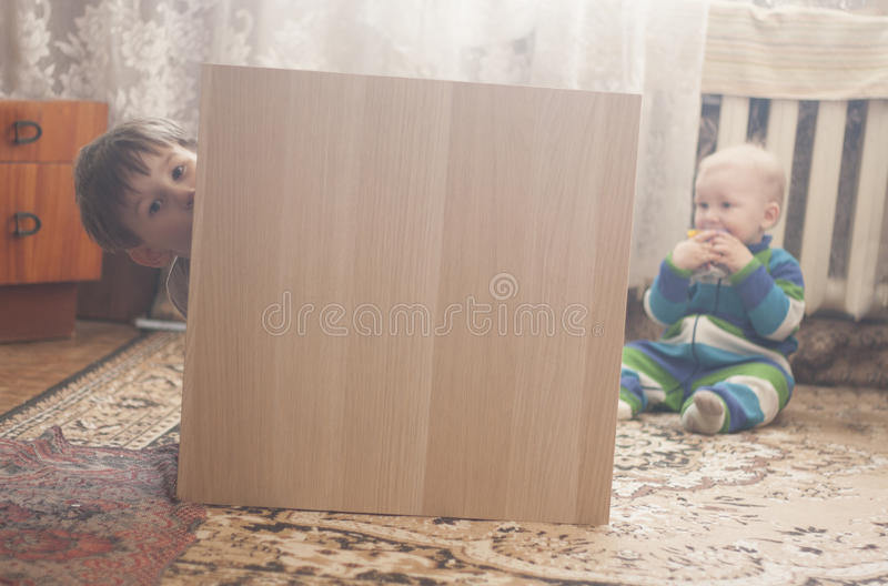 Menino pequeno que esconde atrás da mobília de madeira imagens de stock royalty free