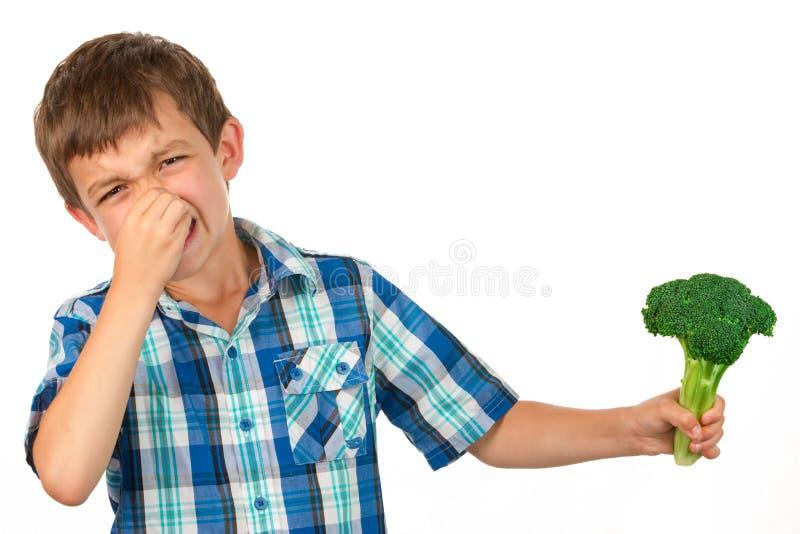 Menino pequeno que guarda um grupo dos brócolis foto de stock royalty free