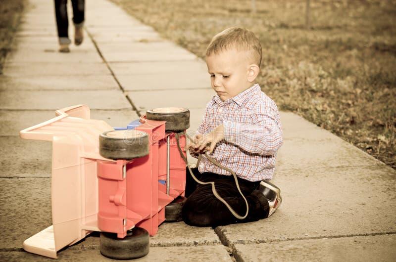 Menino pequeno que joga com um plástico imagens de stock