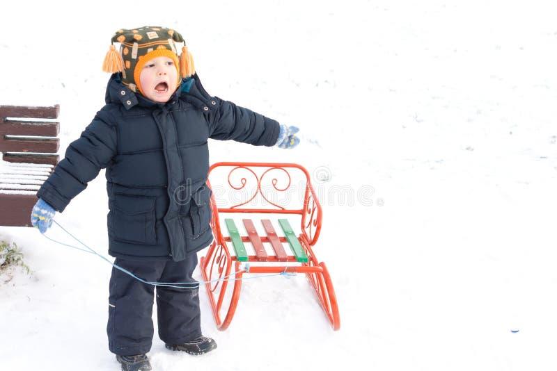 Menino pequeno que joga com um trenó na neve imagens de stock