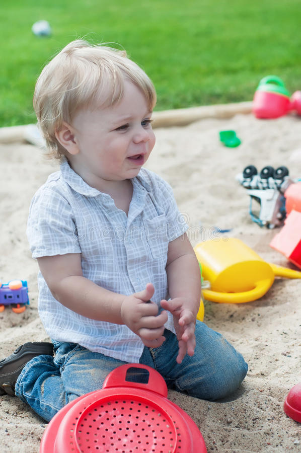 Menino pequeno que joga no sandpit fotos de stock royalty free