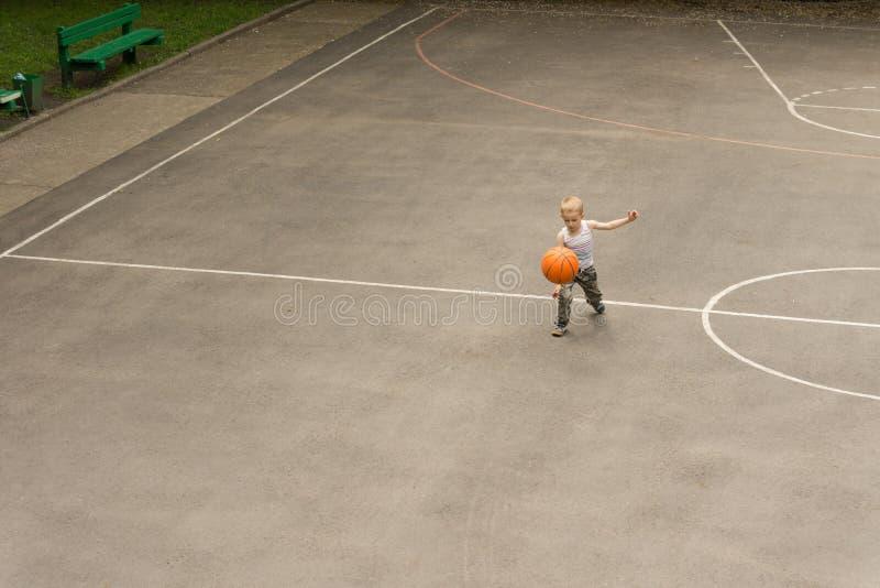 Menino pequeno que joga o basquetebol que salta a bola fotos de stock