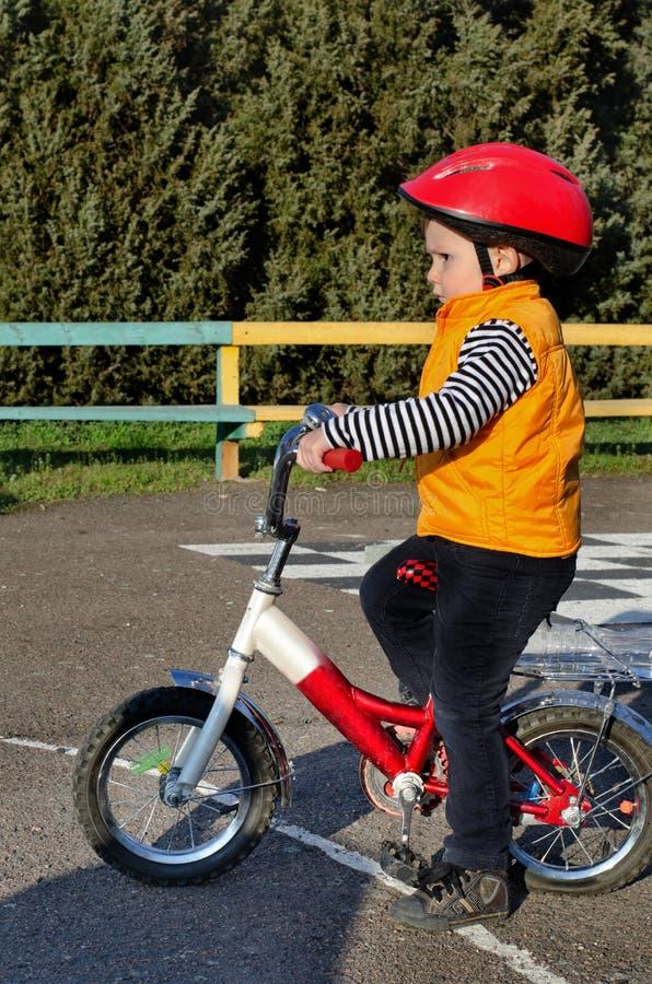Menino pequeno que monta sua bicicleta fotografia de stock