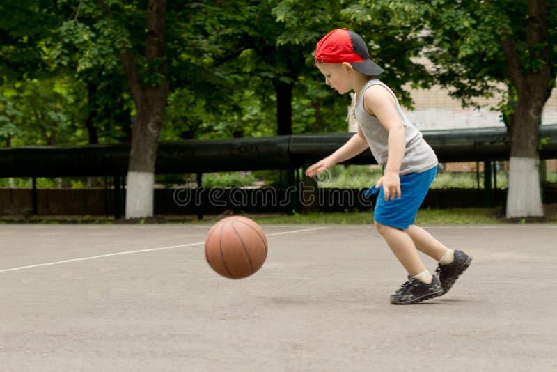 Menino pequeno que salta um basquetebol em uma corte imagens de stock royalty free