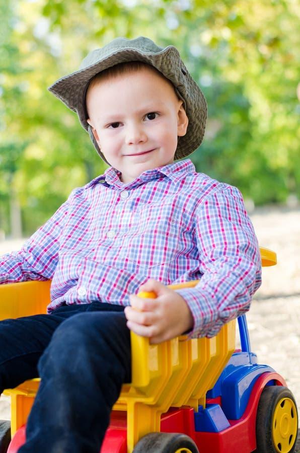 Menino pequeno que senta-se em um caminhão do brinquedo imagem de stock