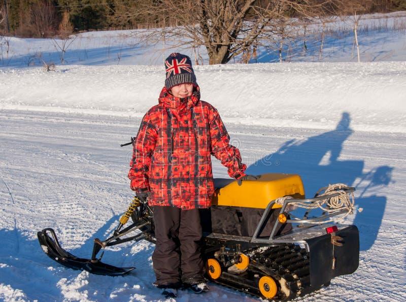 Menino perto de um carro de neve no inverno imagem de stock royalty free