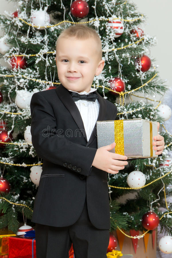 Menino perto de uma árvore de Natal com um presente à disposição imagens de stock