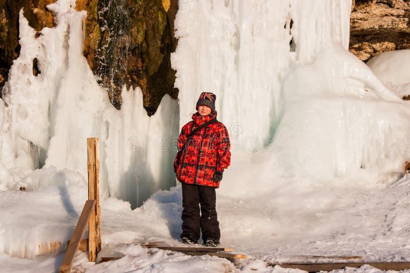 Menino perto do ` de Plakun do ` da cachoeira no inverno em um dia ensolarado fotos de stock royalty free