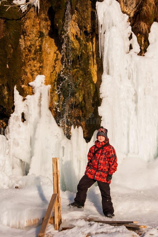 Menino perto do ` de Plakun do ` da cachoeira no inverno em um dia ensolarado imagem de stock