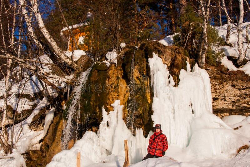 Menino perto do ` de Plakun do ` da cachoeira no inverno em um dia ensolarado fotografia de stock royalty free