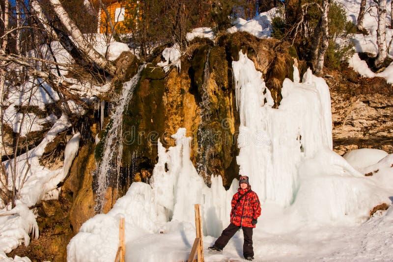 Menino perto do ` de Plakun do ` da cachoeira no inverno em um dia ensolarado imagens de stock royalty free