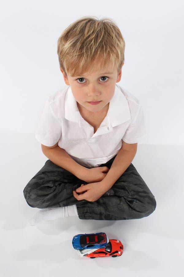 Menino pré-escolar bonito que senta-se com um grupo de brinquedos e que quer saber, que agora? foto de stock