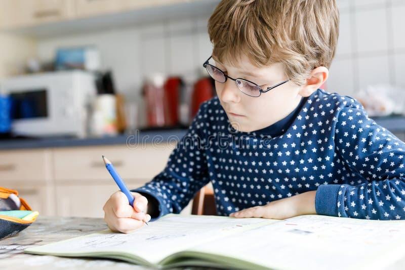 Menino pré-escolar da criança em casa que faz letras da escrita dos trabalhos de casa com penas coloridas foto de stock