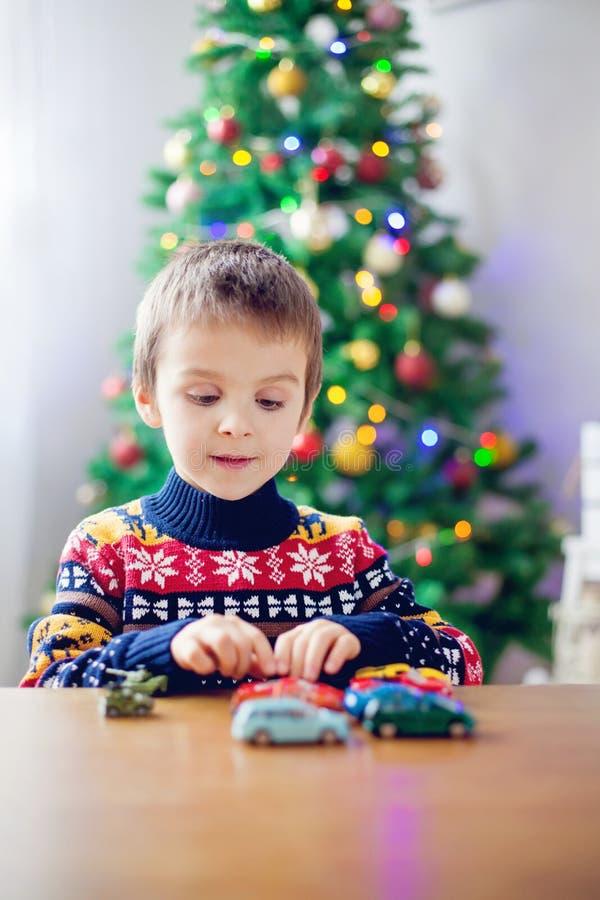 Menino pré-escolar pequeno adorável, jogando com carros do brinquedo em casa sobre imagens de stock