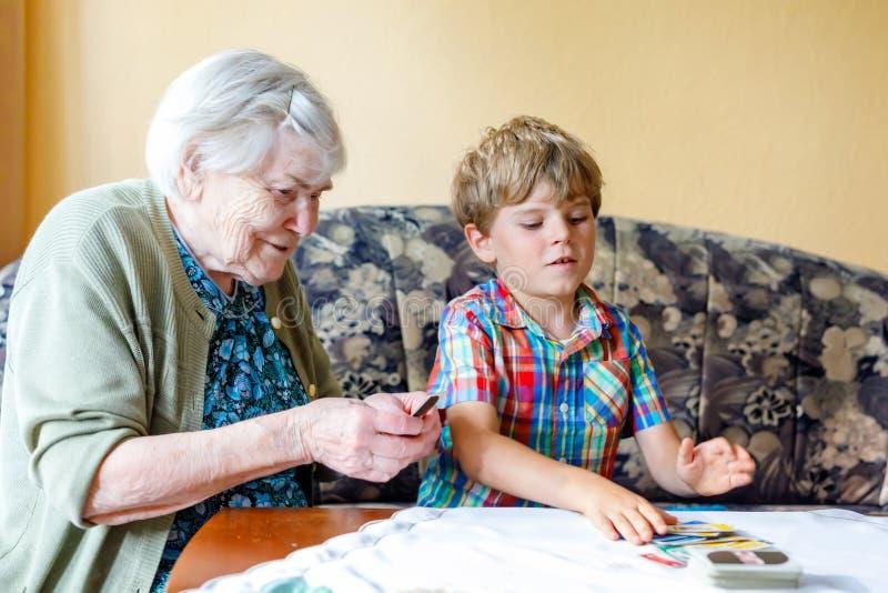 Menino pré-escolar pequeno ativo da criança e avó grande que jogam o jogo de cartas junto em casa fotografia de stock royalty free