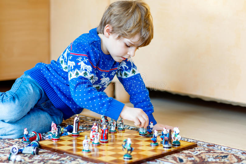 Menino pré-escolar pequeno da criança que joga o jogo de xadrez em casa fotografia de stock