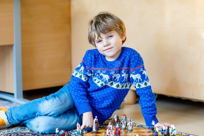 Menino pré-escolar pequeno da criança que joga o jogo de xadrez em casa foto de stock