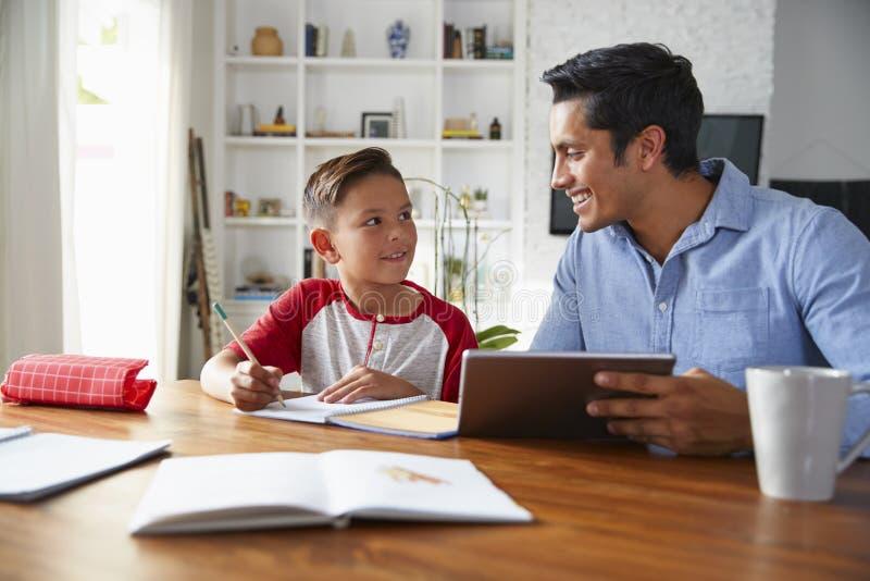 Menino pre-adolescente latino-americano que senta-se na tabela que trabalha com seu tutor da escola da casa, sorrindo em se imagem de stock