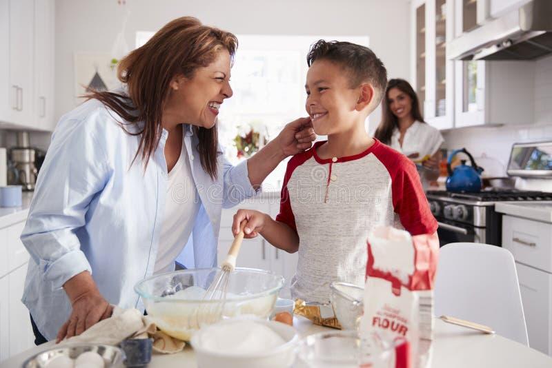 menino Pre-adolescente que faz um bolo na cozinha com sua avó, seu mum que está no fundo imagem de stock royalty free