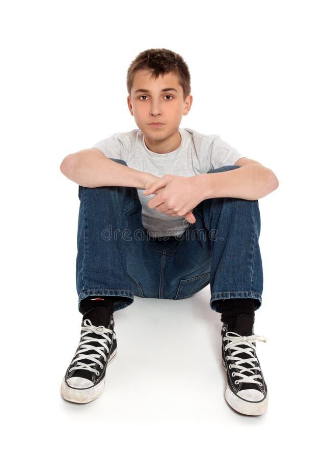 Menino pre adolescente que senta-se nas calças de brim e no t-shirt imagens de stock royalty free