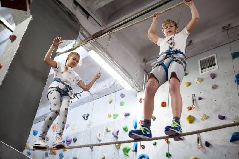 Menino Preteen e menina que equilibram na corda com cabo da segurança, parque de diversões imagens de stock royalty free