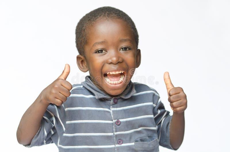 Menino preto africano muito feliz que faz os polegares acima do sinal com as mãos que riem o menino felizmente africano do preto  imagens de stock royalty free