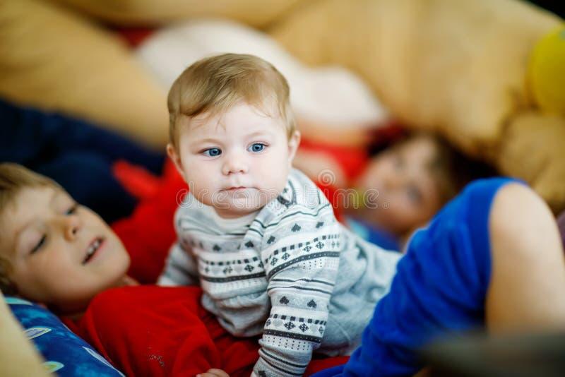 Menino que abraça com bebê recém-nascido, irmã bonito da criança siblings Irmão no fundo Ligamento das crianças Família de fotos de stock
