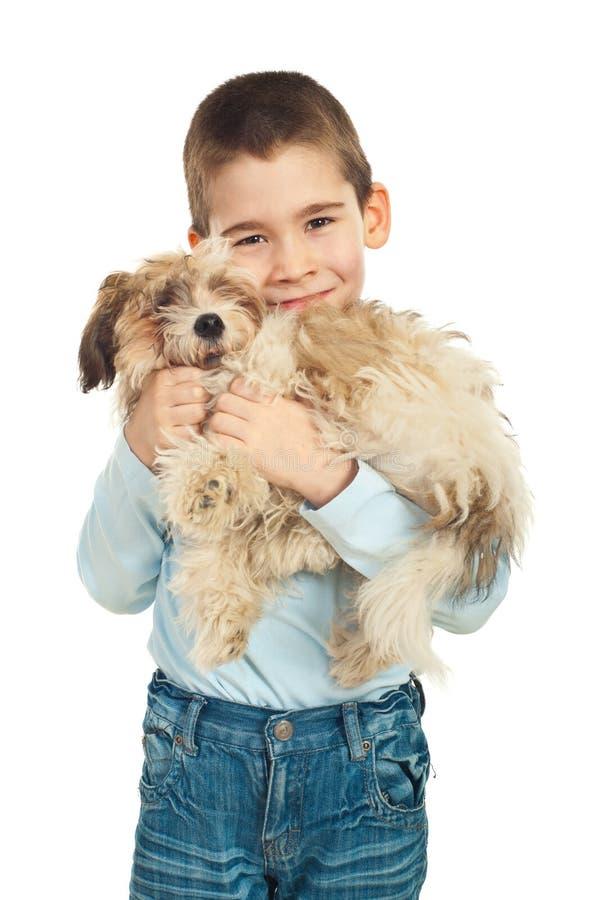 Menino que ama seu cão de filhote de cachorro imagem de stock