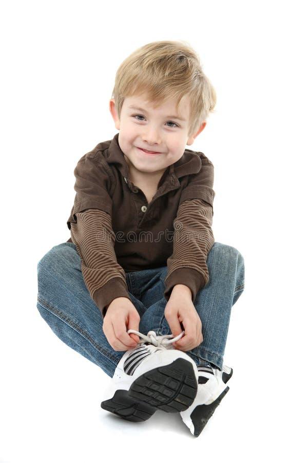 Menino que amarra suas sapatas foto de stock