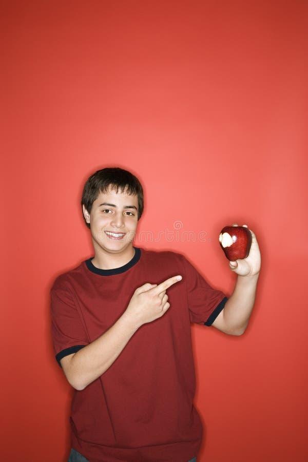 Menino que aponta à maçã comida. imagem de stock