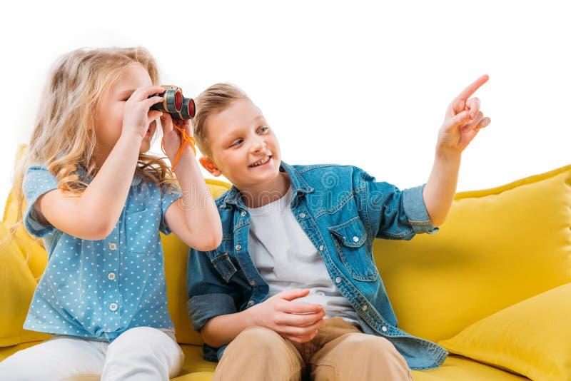 menino que aponta quando irmã que olha os binóculos, sentando-se imagens de stock royalty free