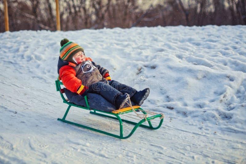 Menino que aprecia um passeio do trenó Crianças que montam um pequeno trenó Brincadeira fora na neve Caçoa o trenó no parque do i imagem de stock