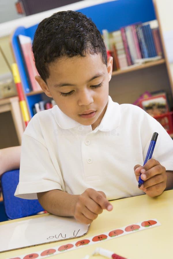 Menino que aprende escrever números na classe preliminar imagem de stock