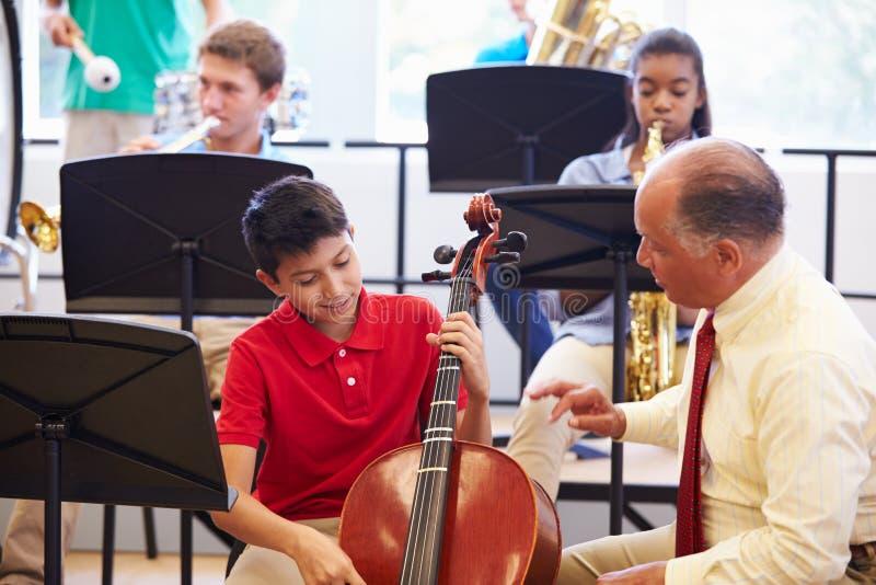 Menino que aprende jogar o violoncelo na orquestra da High School fotografia de stock