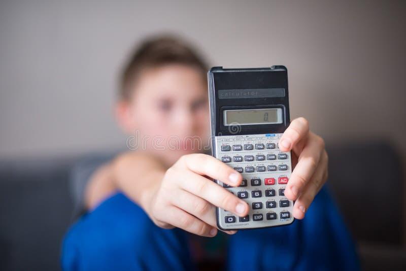 Menino que apresenta a calculadora foto de stock royalty free