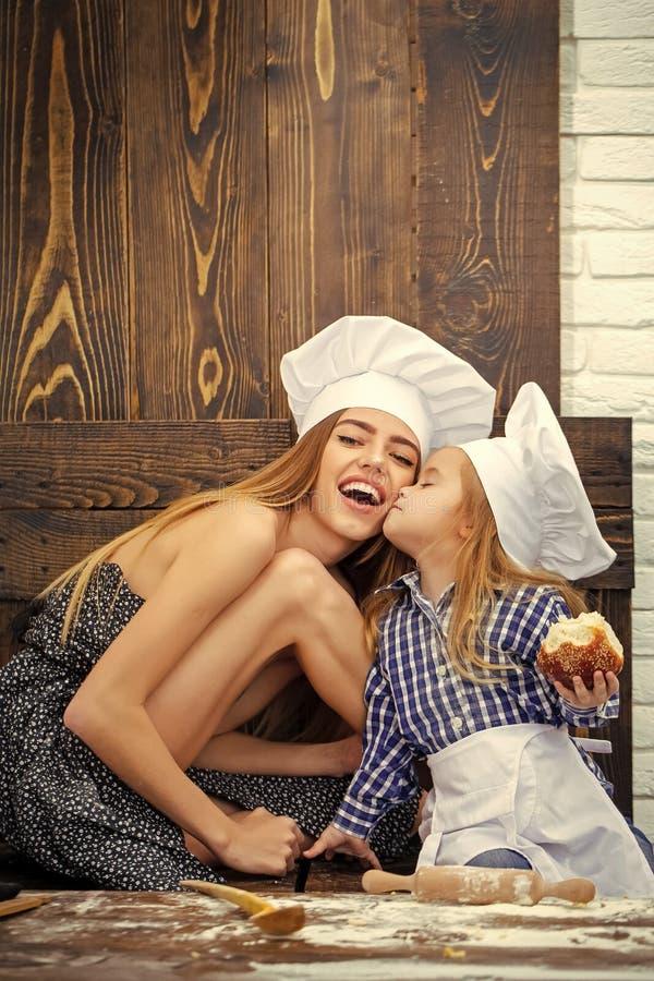 Menino que beija a mulher feliz em chapéus do cozinheiro chefe na cozinha imagens de stock royalty free