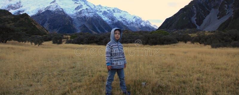Menino que caminha nas montanhas fotografia de stock