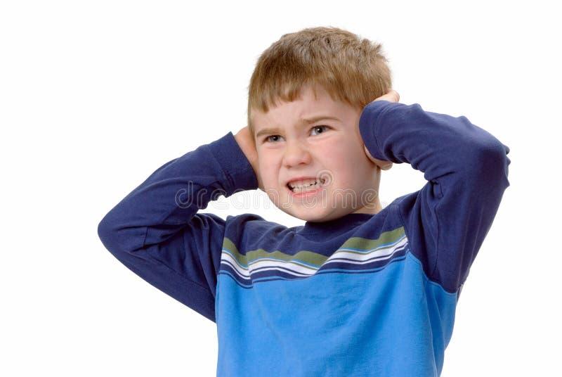 Menino que cobre suas orelhas foto de stock