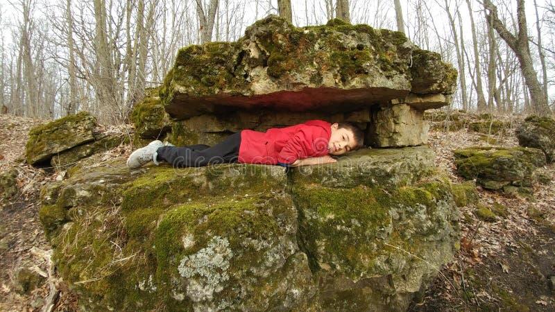 Menino que coloca entre duas rochas - as rochas de Brady foto de stock