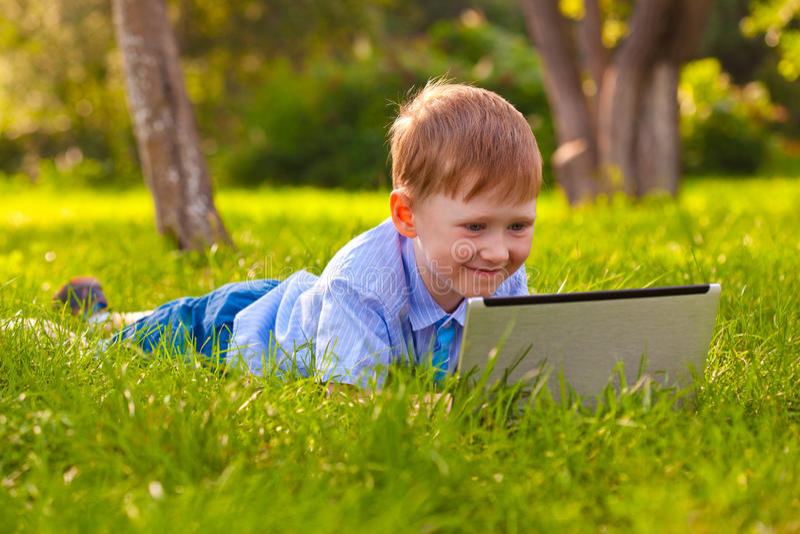 Menino que coloca na grama no parque com portátil fotos de stock