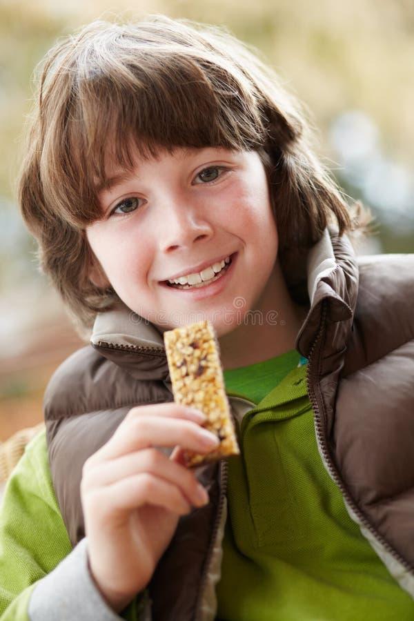 Menino que come a barra saudável do petisco fotos de stock