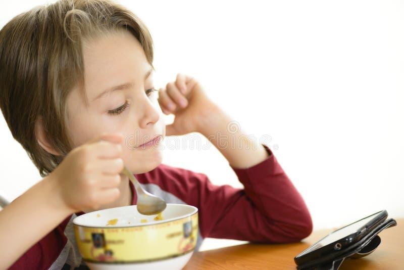 Menino que come cereais imagens de stock